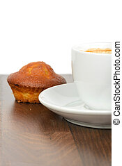 Half cup of coffee with cupcake on table