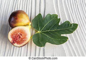 half cut black genoa figs and leaf on grey wooden background