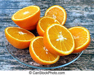 Half cut oranges on wooden background