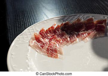 Half decorated arrangement of iberian cured ham on plate