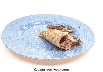 Half eaten pancake on a blue plate