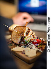 Half Eaten Sandwich On Wooden Plate - Closeup of half eaten...