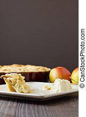 Half eaten slice of apple pie a la mode, vertical