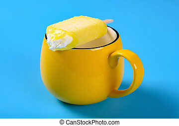half eaten yellow popsicle on a cup on blue background