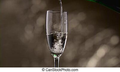 Half empty glass is filled with champagne green bottle. Bokeh background