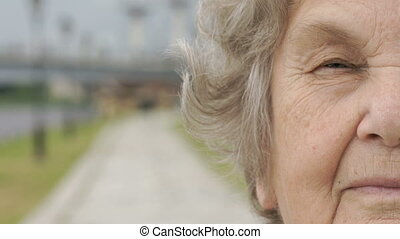 Half face of serious mature old woman outdoors