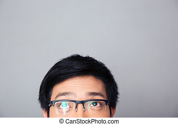 Half face portrait of asian man looking up at copyspace -...