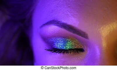 Half female attractive face. Woman blinks eye with beautiful makeup, glitter shadows. Purple bright neon light. Beauty, cosmetics, feminine concept. 4k