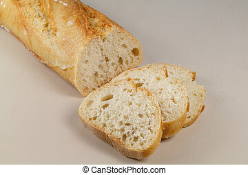 Half French baguette of bread and three slices