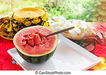 Half fresh and red watermelon fruit and spoon on white tray on table with yellow summer hat and plumeria or frangipani flowers with sea conch shell in background, watermelon in sunny day with mood of relaxing in summer vacation