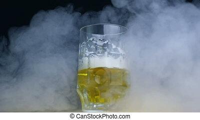 half full glass of pilsener or lager beer spinning in smoke...