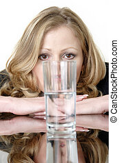 Woman looking intensely at a glass half full or half empty glass of water