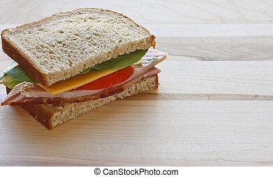 Half Ham and Cheese Sandwich on Wood Cutting Board