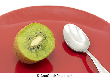 Half kiwi fruit ready to eat with a spoon