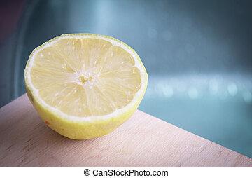 Half lemon cut on wooden cutting board