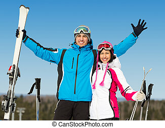 Half-length portrait of embracing downhill skiers -...