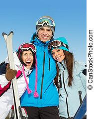 Half-length portrait of group of hugging skier friends