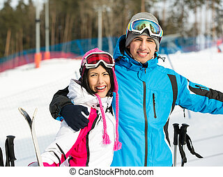 Half-length portrait of two embracing skiers who wear goggles and sports jackets