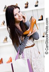 Half-length portrait of woman handing heeled shoe
