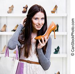 Half-length portrait of woman handing high heeled shoe