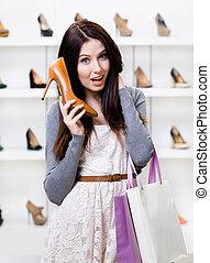 Half-length portrait of woman handing shoe