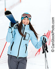 Half-length portrait of woman handing skis