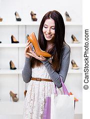 Half-length portrait of woman keeping heeled shoe