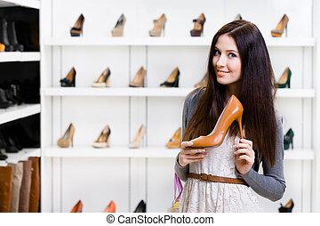 Half-length portrait of woman keeping high heeled shoe