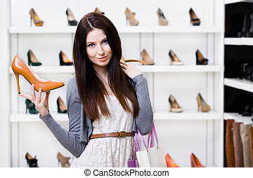 Half-length portrait of woman keeping stylish pump