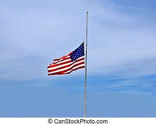 American flag at half-mast against a misty blue sky