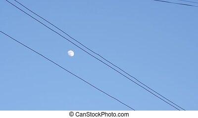 half moon in a blue evening sky seen through diagonal wires.