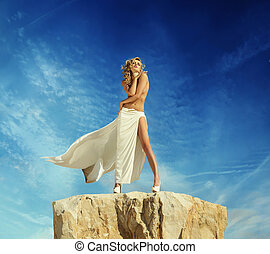 Half-naked blonde posing on the top of the mountain
