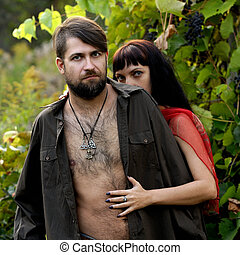 Half naked man and woman in wild grapes
