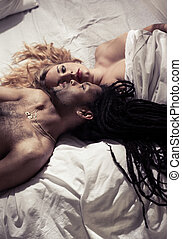 Half naked mixed couple lying in bed
