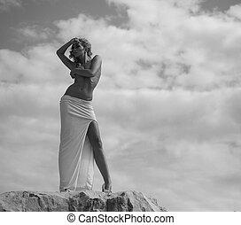 Half-naked woman looking at the rocks