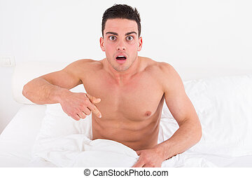 half naked young man in bed looking down at his underwear at...
