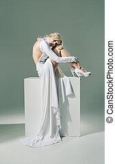 Half nude woman wearing white dress