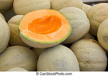 ripe muskmelon - Half of a ripe muskmelon on a pile of...