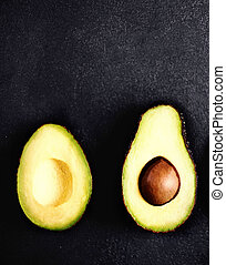 Half of avocado on a black background with cop space for text, top view