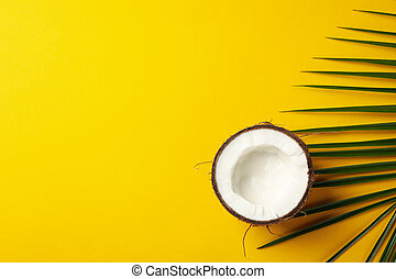 Half of coconut and palm leaf on yellow background, top view