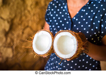 Half of coconut in woman's hands on rustic background