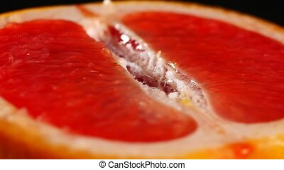 Half of grapefruit, rotating on a black background