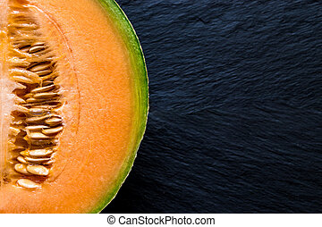 Half of Hami Melon Fruit on Black Stone Background Surface with Free Space