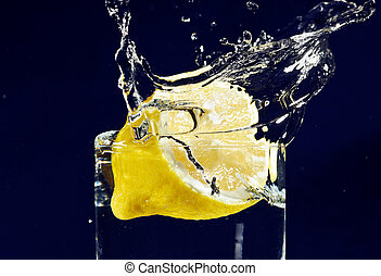 Half of lemon falling down in glass with water on deep blue