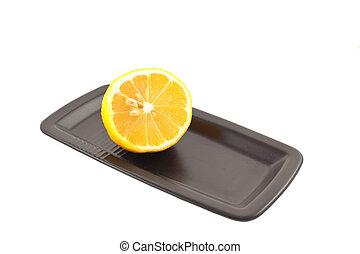 half of lemon on a black square plate