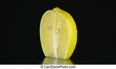 Half of lemon, rotating on a black background