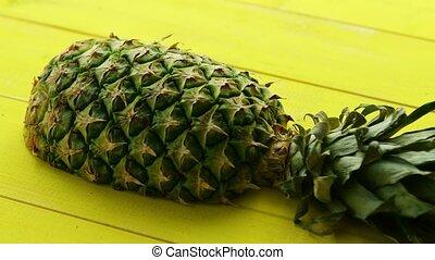 Half of pineapple on yellow wood - Cut half of unpeeled...