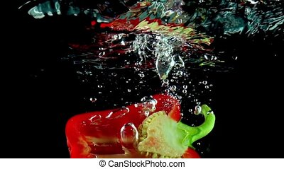 Half of red bell pepper falls into water and flips super slow motion shot