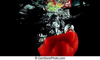 Half of red sweet pepper falls into water close up super slow motion shot