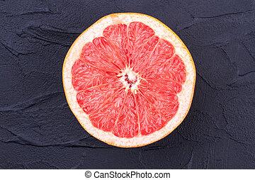 Half of ripe grapefruit on black background.